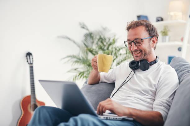 Mann, der Musik hört und Laptop im Wohnzimmer benutzt. – Foto