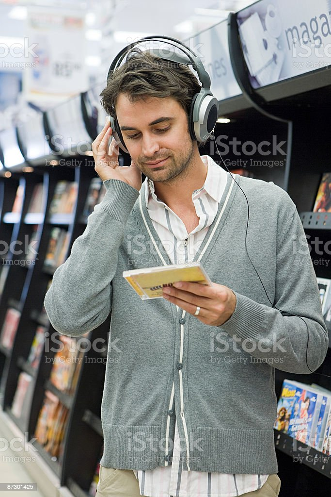 Man listening to music in supermarket royalty-free stock photo
