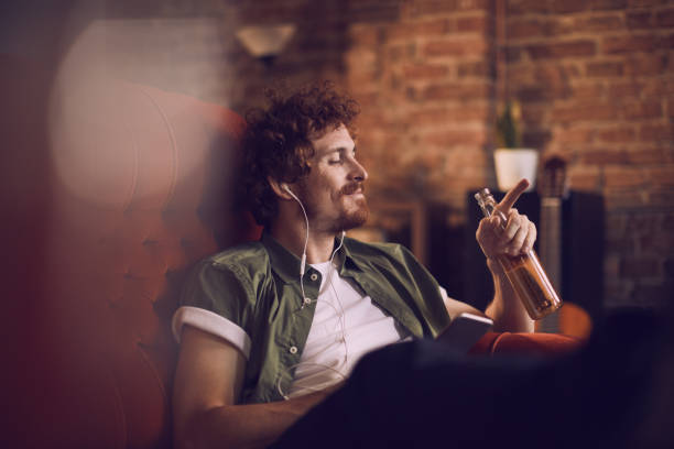 Man listening to music Close up of a young man listening to music and having a beer beer alcohol stock pictures, royalty-free photos & images