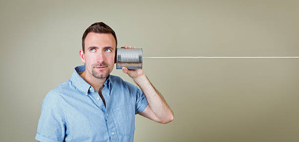 Man listening to tin can telephone
