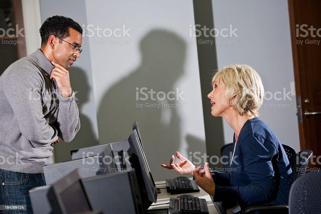 Man listening to woman using computer stock photo