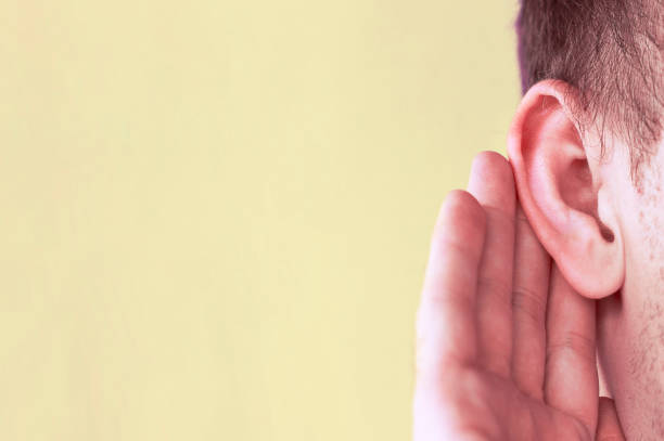 Man listens attentively with her palm to her ear, close up, news concept stock photo
