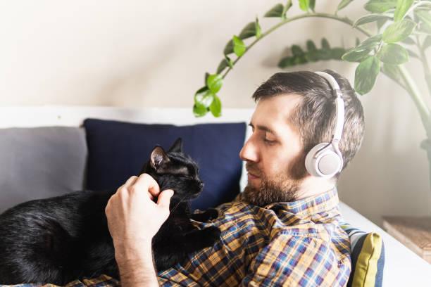 Man listens to music in headphones on the sofa at home looking at picture id1208352313?b=1&k=6&m=1208352313&s=612x612&w=0&h=suq7bcuzwj8n3zikprytp8cd ybjuhfi27ylmbbsoha=