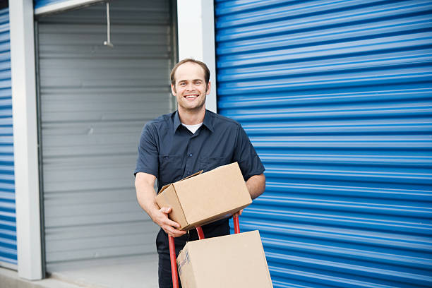 Man loading boxes for moving company at a self storage place stock photo