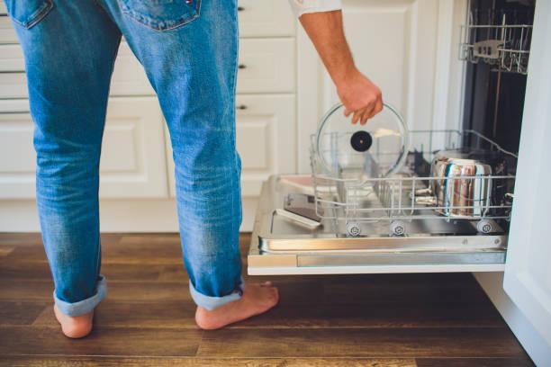 Mann laden Geschirrspüler in Küche – Foto