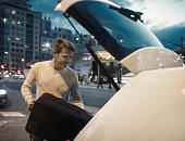 Man loading luggage in car trunk