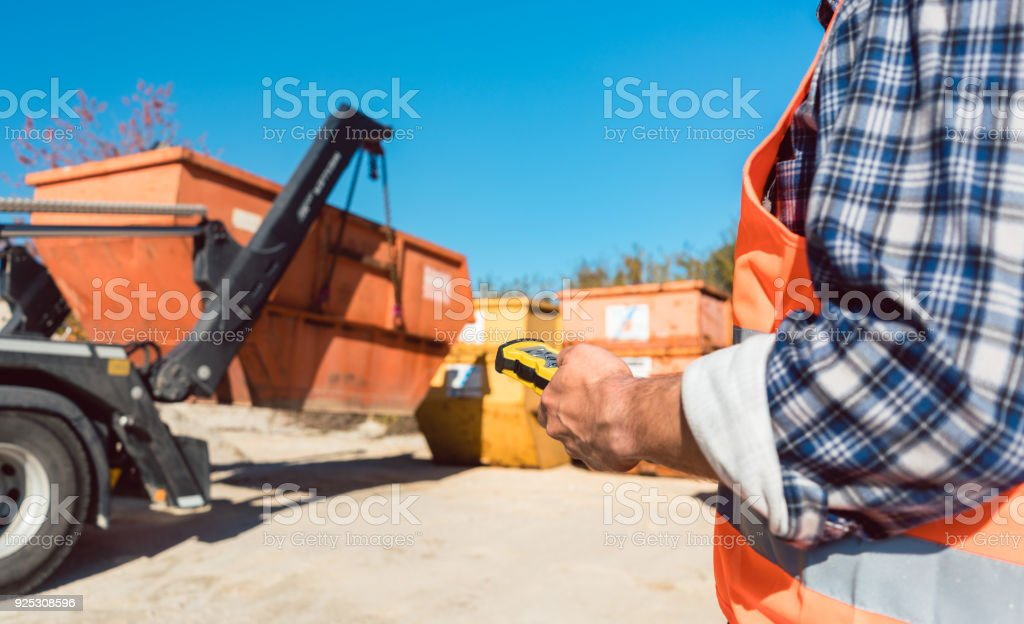 Man loading of construction debris container on truck stock photo