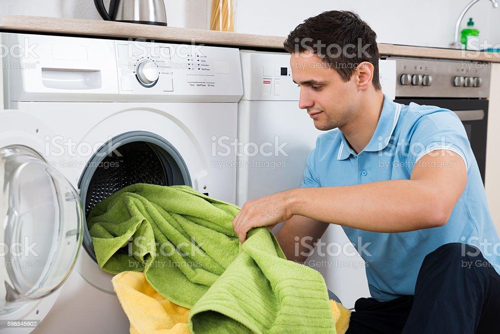 Man Loading Towels In Washing Machine photo libre de droits