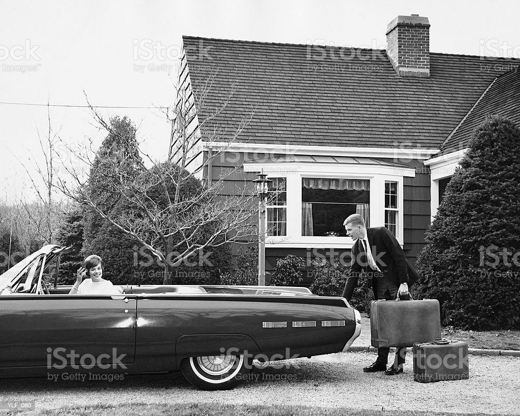 Man loading trunk with suitcases while woman waits in car royalty-free stock photo