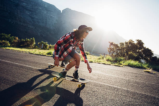 Man longboarding outdoors on countryside road stock photo