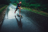 Young Caucasian man longboarding in forest