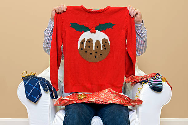 Man - Look what I got for Christmas A man opening Christmas presents to discover he got a Christmas themed jumper to go along with the usual socks and tie. negative emotion stock pictures, royalty-free photos & images