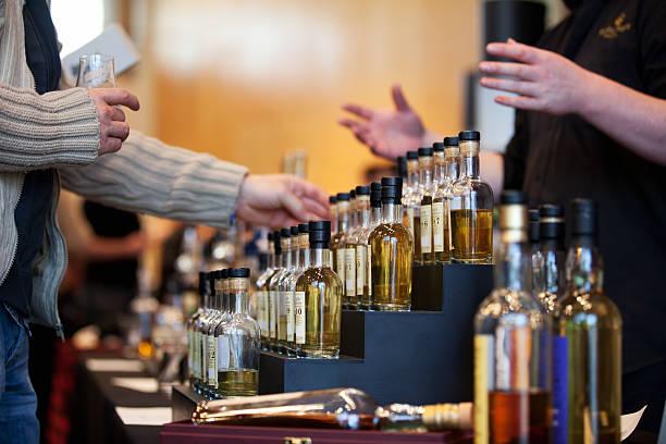 man looking at a whiskey bottle display - tasting stockfoto's en -beelden