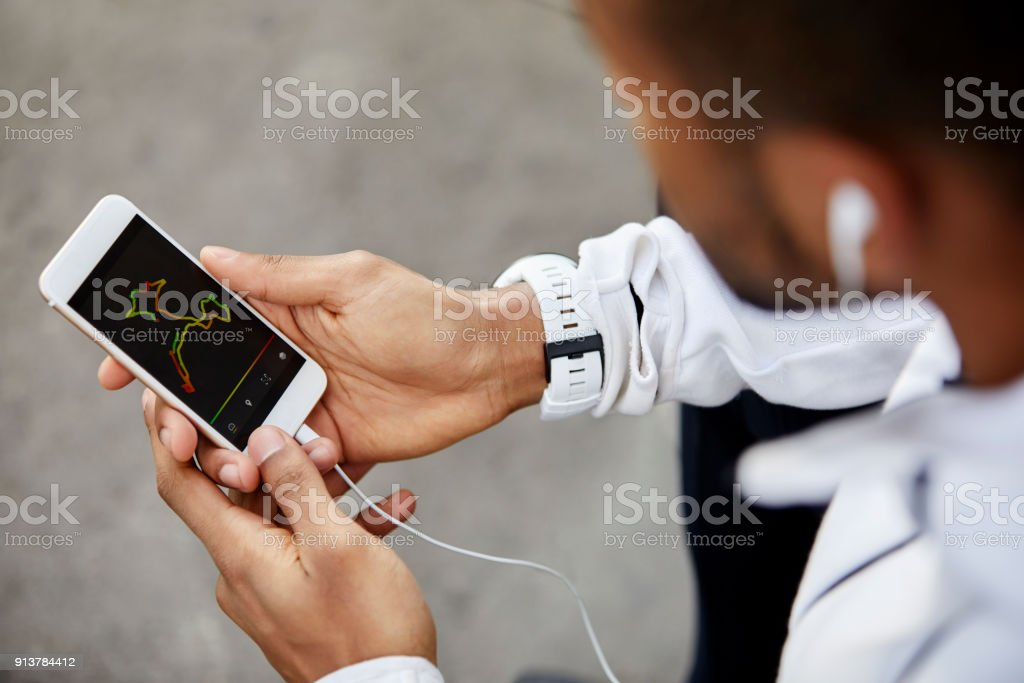 Man looking at analysis on screen of smart phone stock photo