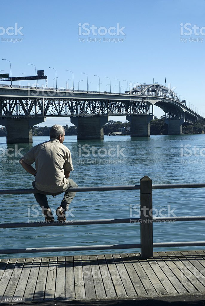 Man looking at Auckland Harbour Bridge stock photo