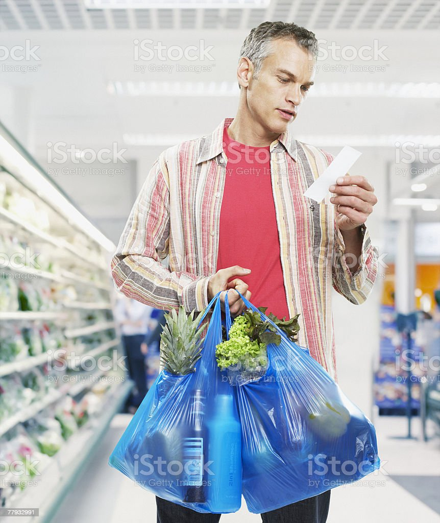 Man looking at bill in grocery store stock photo