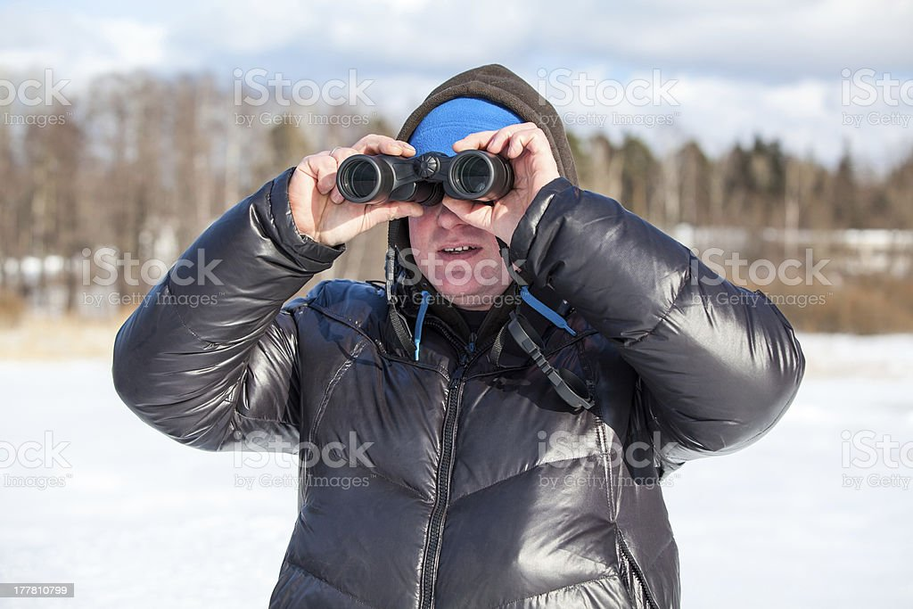 Man looking at binocular in warm winter clothes outdoor royalty-free stock photo