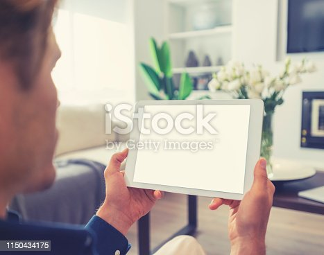 Man looking at blank digital tablet. He is sitting in his living room on a sofa. Rear view over his shoulder so we can see the screen.