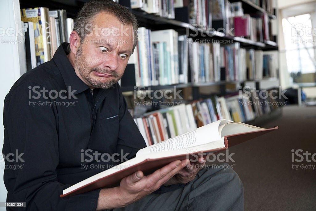 Man Looking at Book in Library Making a Face royalty-free stock photo