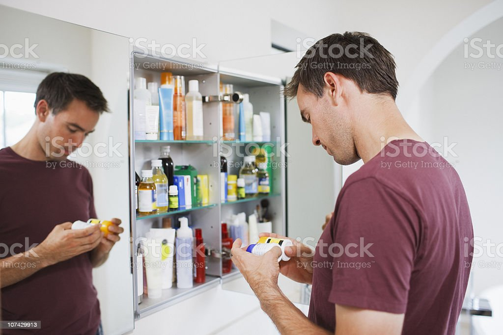 Man looking at bottles from medicine cabinet stock photo