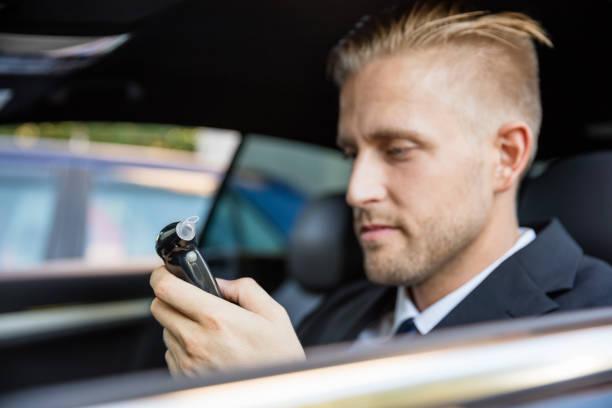homem olhando para o teste do bafômetro - bafometro - fotografias e filmes do acervo