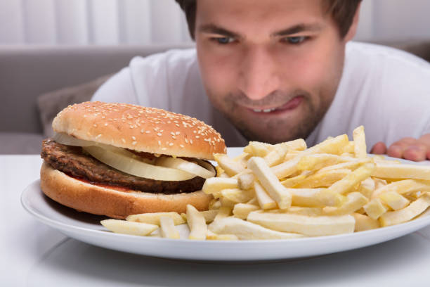 man tittar på hamburgare och pommes frites - cravings bildbanksfoton och bilder