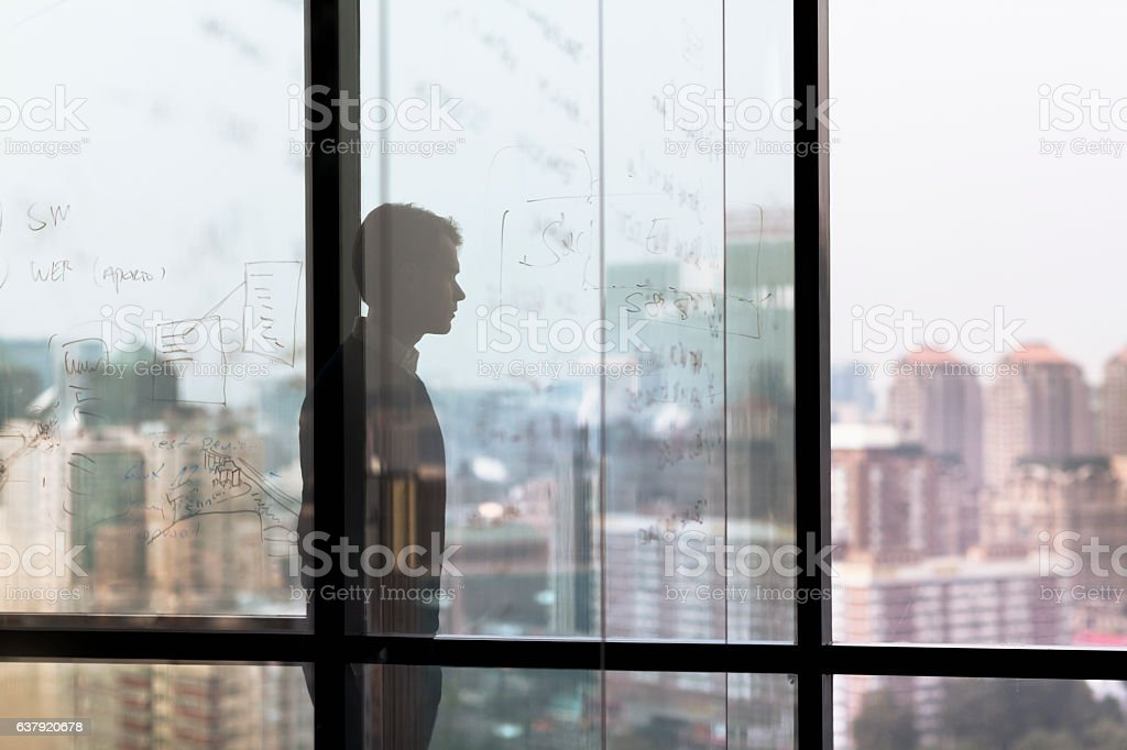 Man looking at city from window in business office stock photo