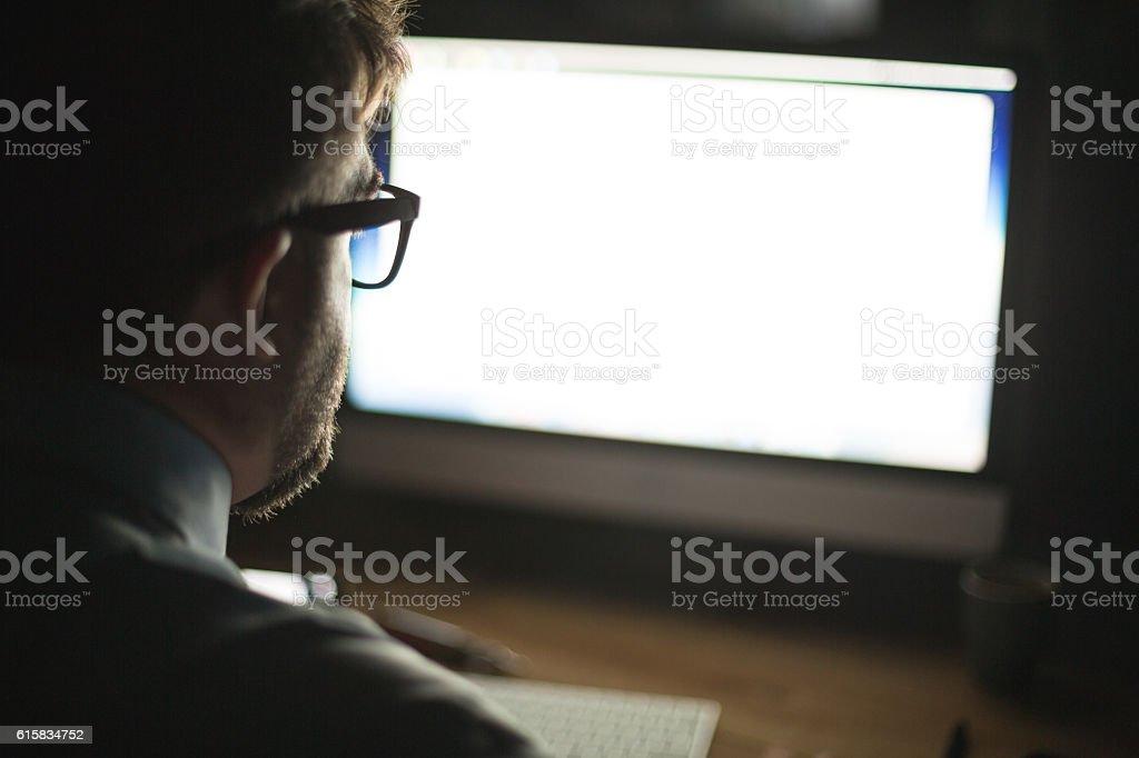 Man looking at computer monitor stock photo
