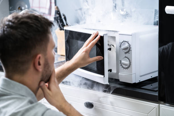 man looking at fire coming from microwave oven - burned oven imagens e fotografias de stock
