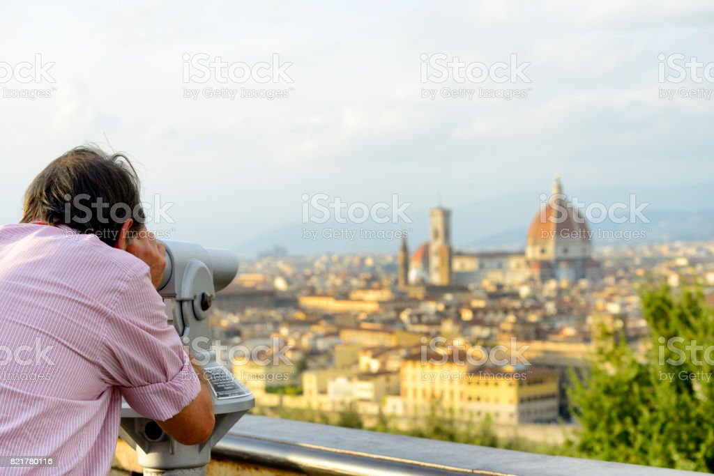 Man looking at florence with binoculars stock photo