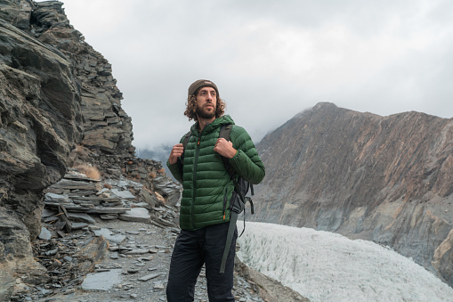 Young Caucasian man in knitted sweater  looking at glacier in Pakistan
