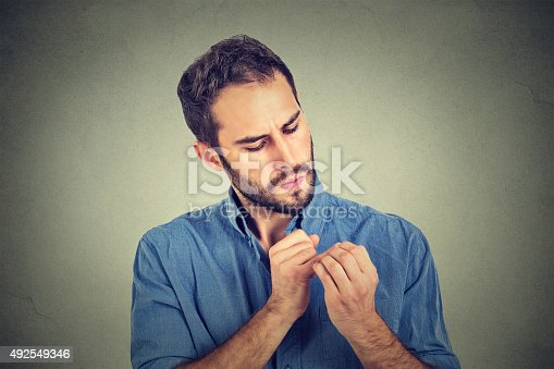 istock man looking at hands nails obsessing about cleanliness germs 492549346
