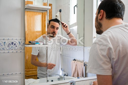 istock Man looking at himself in a mirror in the bathroom. He is combing his hair 1161582509