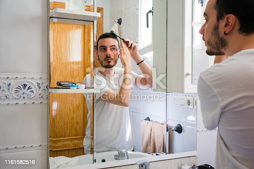 istock Man looking at himself in a mirror in the bathroom. He is combing his hair 1161582516