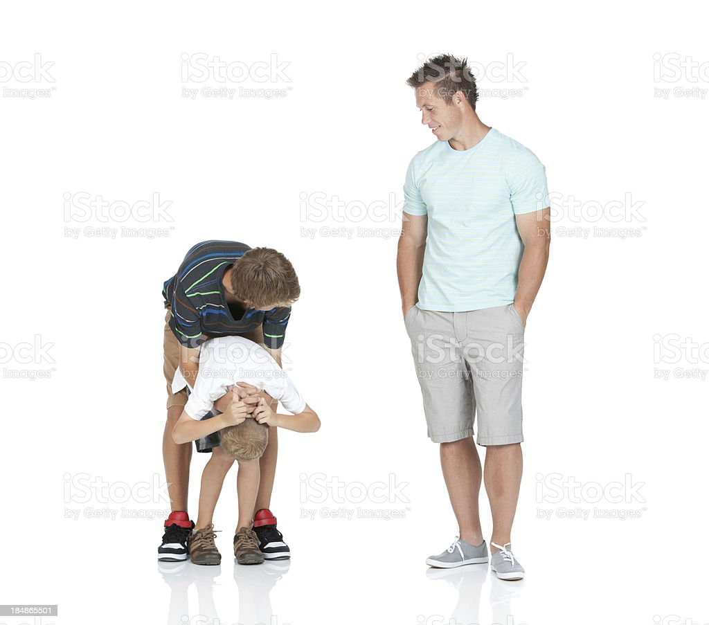 Man looking at his children playing stock photo