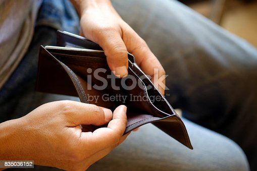 istock Man looking at his empty leather wallet in office. 835036152