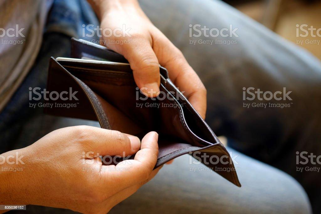 Mann sucht in seiner leeren Leder Brieftasche im Büro. – Foto