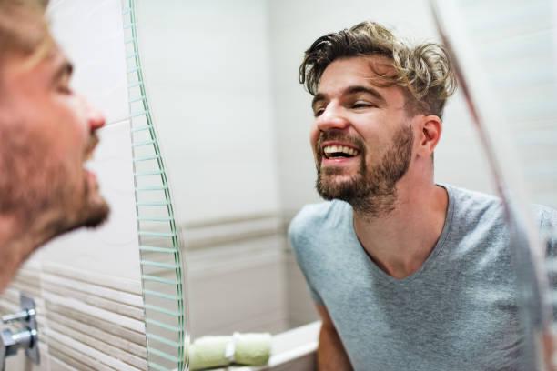 man looking at his face in the mirror - covid hair imagens e fotografias de stock