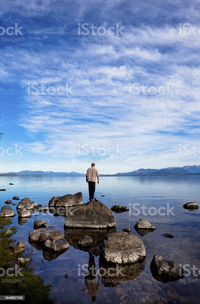 Man looking at his reflection in a mountain lake royalty-free stock photo