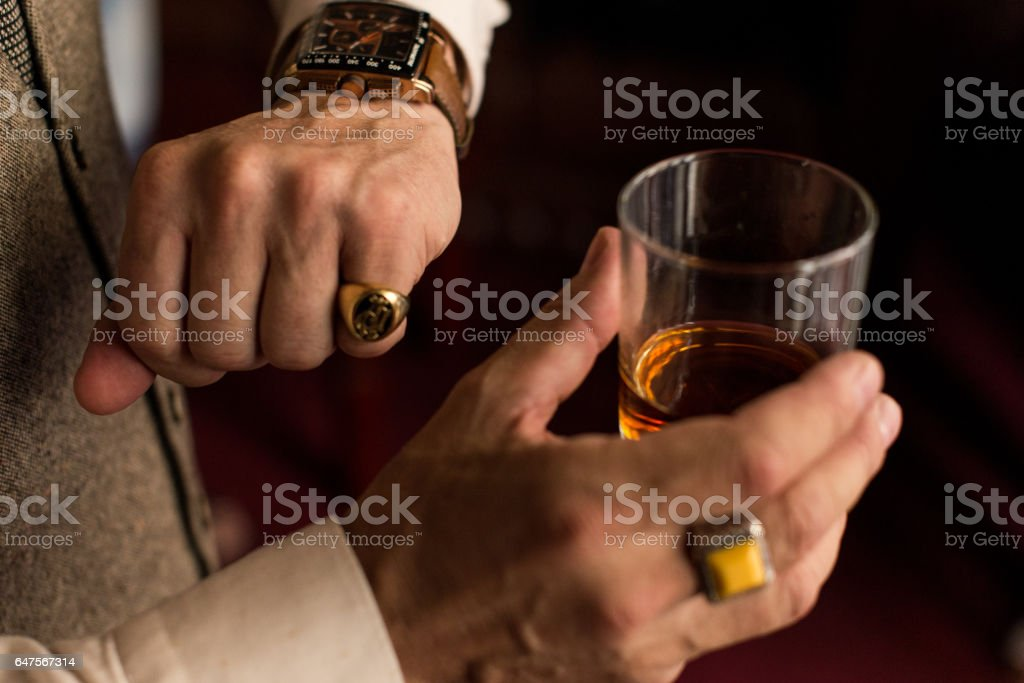 Man looking at his stylish watch on the left hand with a ring on the little finger. In right hand he holding a glass of whiskey. stock photo