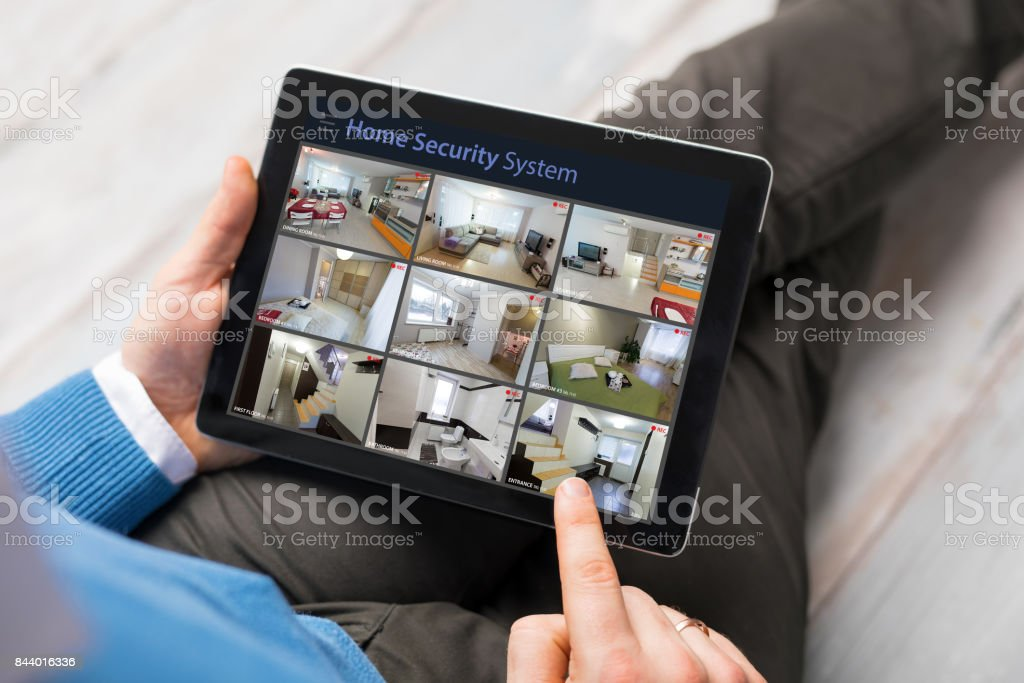 Man looking at home security cameras on tablet computer stock photo