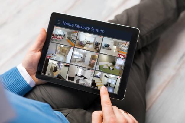 Mann auf der Suche zu Hause Überwachungskameras auf dem Tablet PC – Foto