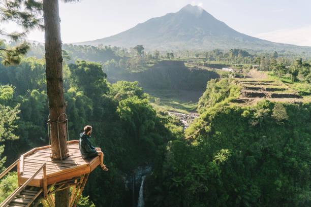 Man looking at Kedung Kayang waterfall and Merapi mountain on Java stock photo