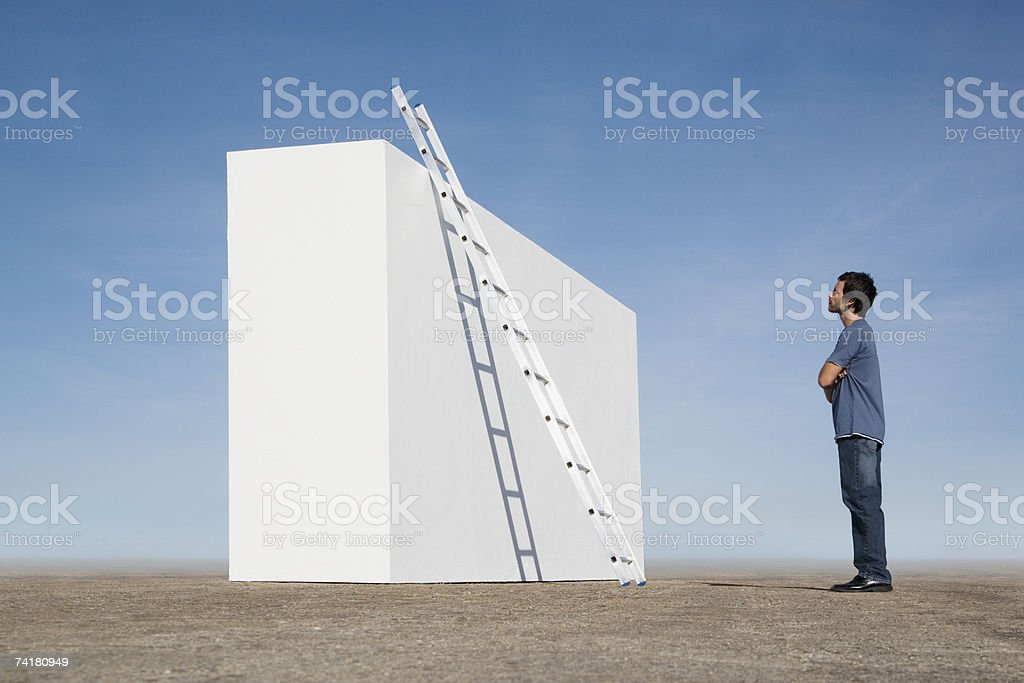 Man looking at ladder against wall outdoors royalty-free stock photo