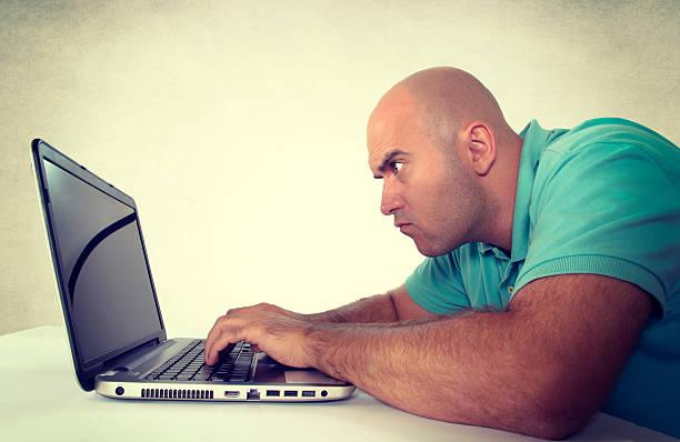 Man looking at laptop computer stock photo