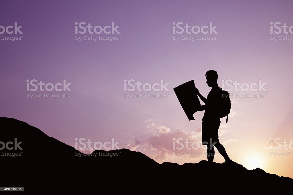 Man looking at map in nature while hiking royalty-free stock photo