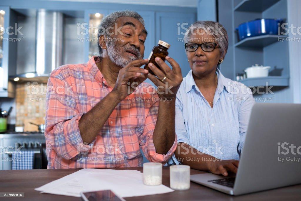 Hombre mirando la medicina mientras que se sienta mujer usando laptop - foto de stock