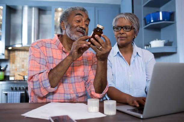 mann, die medizin zu betrachten, während der sitzung von frau mit laptop - südafrikanische rezepte stock-fotos und bilder