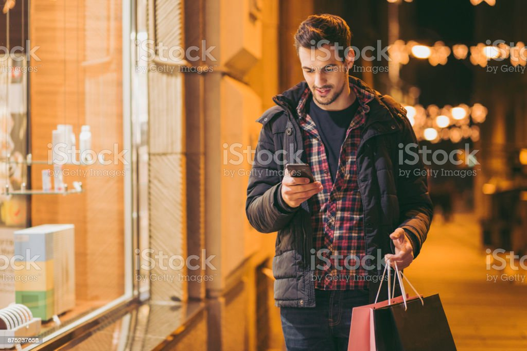 Man looking at mobile phone near shopping window stock photo
