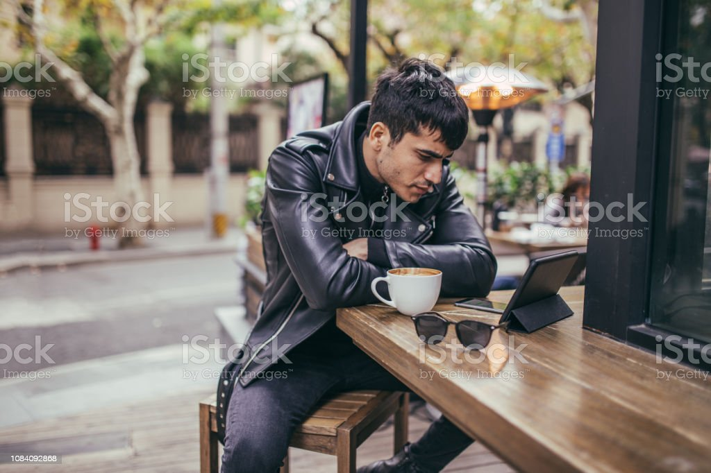 One young handsome man in black outfit on a coffee break looking at...